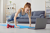 Online sport exercises at home. Workout at home. Redhead girl doing exercises at home.