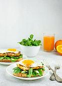 European breakfast Sandwich with fried egg, chicken, herbs and orange juice. A sandwich. Breakfast on a light table, side view.