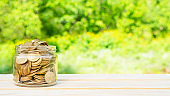 Business concept. Coins in a jar on a wooden table. Business ideas. Recovery and business growth. Copy space
