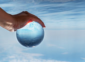"""Crystal ball in the man""""u2019s hand. Original upside down view and rounded perspective of the sky and sea."""