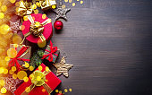 Christmas decoration, gift boxes and blurred lights on dark wooden table. Christmas or New Year holiday background shows the magic of Christmas holiday.
