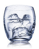 Glass of vodka or gin, chilled alcohol drink, with ice cubes isolated on white background. Clipping path.