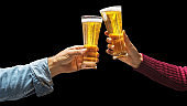 Toasting with beer glasses. Man and woman hands lifting glasses of beer on black background. File contains a clipping path.