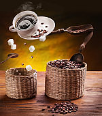 Coffee concept image. Cup of coffee with sugar cubes and coffee beans  flying in the air.