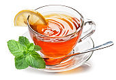 Glass cup with black tea, a slice of lemon and mint leaves isolated on a white background.