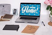 Laptop with stay home announcement on display, pad with stylus, etc on desk