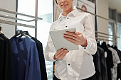 Saleswoman using tablet in clothing store