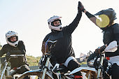 Excited motorcyclists giving high five