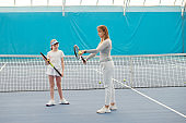 Cute teenage girl in sportswear looking at female trainer and listening to her