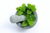 Mint leaves in stone mortar and pestle on white background.