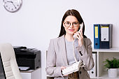 Young busy brunette female office manager in eyeglasses and formalwear