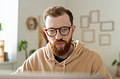 Bearded programmer working with laptop