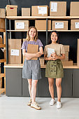 Two young cheerful workers of storage room or office of modern online shop
