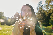 Young Asian woman with long dark hair blowing at dandelion while having fun