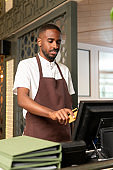 Young waiter or cashier in brown apron entering order of client in computer