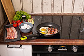 Frying pan with fried eggs and bacon on stove with fresh fruit and vegs near by