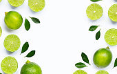 Frame made of fresh limes with leaves isolated on white background.