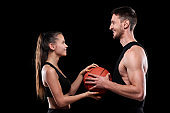 Cheerful sporty couple in activewear holding ball while looking at each other