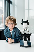 Cute little scientist in eyeglasses and formalwear standing by microscope