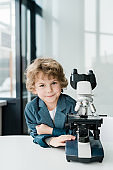 Cute little successful scientist looking at you while standing by microscope