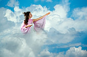 Young girl praying in the clouds