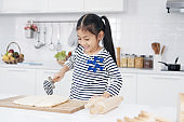 Smiling Asian little asian girl child is learning and enjoying for baking cookies bakery on wooden Cutting board in kitchen. Homemade pastry for bread. Family love and Homeschool.