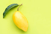 Top view of yellow mango on green background.