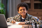 Cheerful little African schoolboy making notes in copybook and looking at you