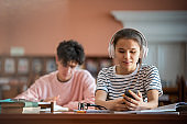 Pretty college student with headphones scrolling in smartphone in library