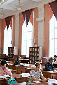 Teenage student scrolling in smartphone by desk in college library