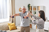 Young female social worker helping aged man exercising with dumbbells