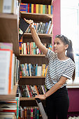 Casual female teenager standing by bookshelf in college library and taking book