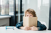 Cute happy little schoolboy peeking out of open book at lesson of literature