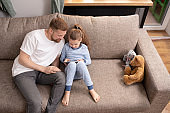 Adorable child in blue pajamas and her father watching online movie