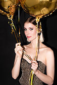 Young elegant blond woman with golden color balloons enjoying birthday party