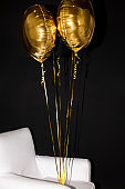 Bunch of inflated golden color balloons bound to white leather armchair