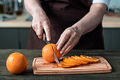 Chef cutting orange on wooden board