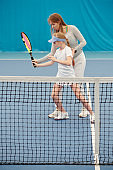 Young female tennis trainer holding racket in hand of girl while consulting her