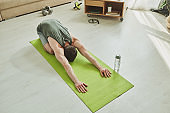 Young muscular athlete doing relaxation exercise on mat while standing on knees