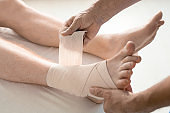 Hands of rehabilitation clinician wrapping foot and ankle of man with bandage