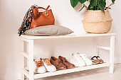 Part of corridor in a flat with footwear, bag and basket on shelves along wall