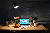 Workplace by window in dark room with items on table and lamp above them