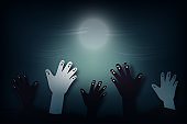 Halloween background in spooky night paper art style.Zombie hand rising from graveyard.