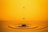 Golden Oil Drops on Yellow Background.