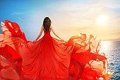 Woman Rear view in Red Flying Dress Fluttering on Wind, Girl in Waving Gown on Sundown Sea