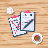 Plan B written in a clipboard isolated on a wooden table