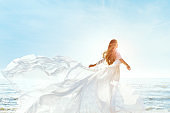 Woman on Sunny Sea Beach in White Fluttering Dress, Fashion Model Back Rear View, Silk Cloth Waving on Wind