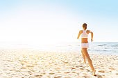Woman Running on Sunny Sea Beach, Rear Back View, Jogging Girl in White Sexy Sport Clothes