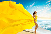 Beautiful Woman in Summer Sexy Dress on Sea Beach, Gown Cloth Waving Fluttering on Wind, Outdoor Portrait