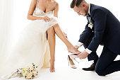 Wedding Couple, Elegant Groom in Suit wearing shoe to Bride Leg in White Dress